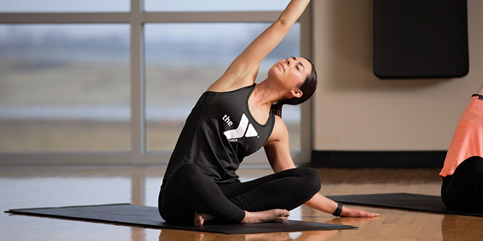 A yoga teacher on YMCA 360 teaches a digital fitness class, stretching in a pose while closing her eyes