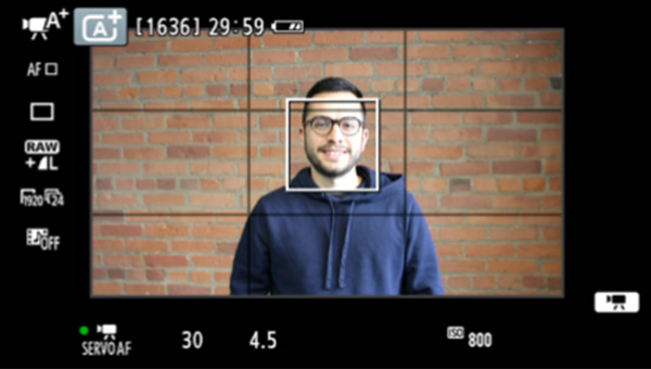 A man stands smiling with a brick wall behind him. The camera display icons see in a square formation all around him