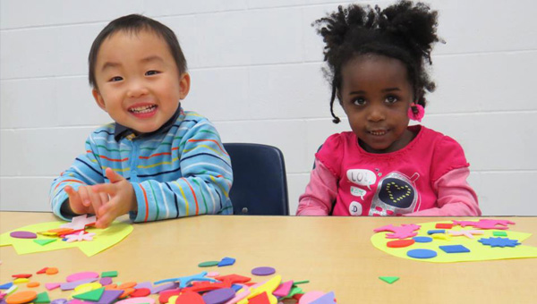 Chinese boy and Afro-american girl sitting on the desk